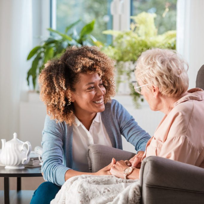 Female home caregiver talking with senior woman, sitting in living room and listening to her carefully.
